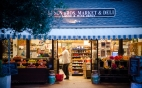 Locals gather in the warm light of a Carmel-by-the-Sea neighborhood market & deli