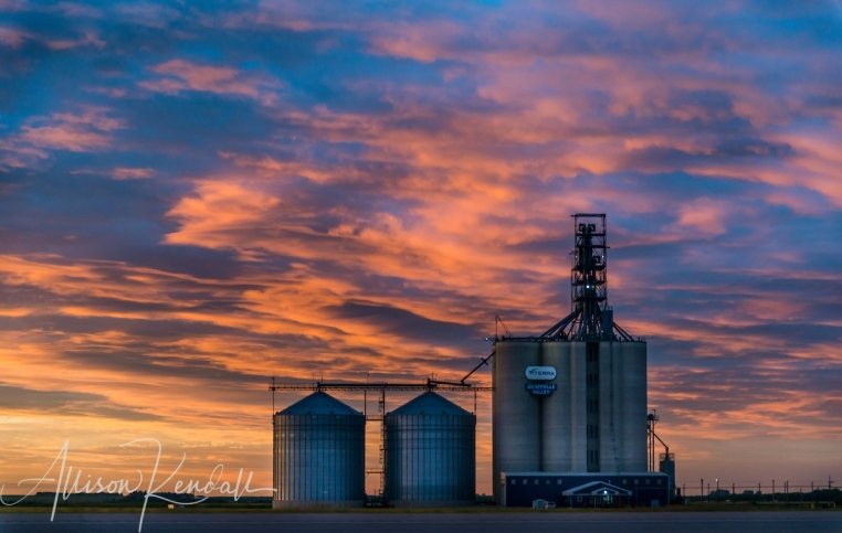 A stunning summer sunset fills the sky above the open Saskatchewan landscape