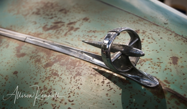 Detail of green paint and patina, and chrome hood ornament of a vintage Buick, seen at the Carmel-by-the-Sea Concours on the Avenue event during Monterey Car Week