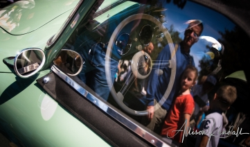 Spectators admiring vintage automobiles at the Carmel Concours on the Avenue event during Monterey car week are reflected in the windows of a classic Porsche