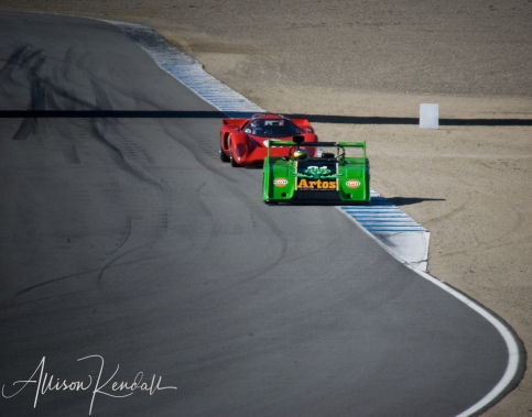 Two vintage racecars battle for position on the Laguna Seca racetrack, Monterey CA