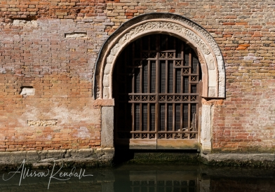 A gated, arched palazzo door and textural brick seen along the canals of Venice, Italy